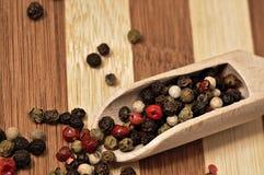 Зерна покрашенного перца на деревянной планке Стоковое Изображение