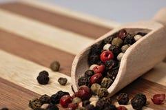 Зерна покрашенного перца на деревянной планке Стоковое Изображение RF