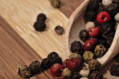 Зерна покрашенного перца на деревянной планке Стоковые Фотографии RF