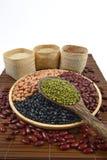 Зерна хлопьев и фасоли семян полезные для здоровья в деревянных ложках на белой предпосылке Стоковые Фотографии RF