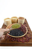 Зерна хлопьев и фасоли семян полезные для здоровья в деревянных ложках на белой предпосылке Стоковая Фотография