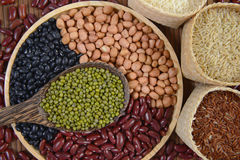 Зерна хлопьев и фасоли семян полезные для здоровья в деревянных ложках на белой предпосылке Стоковое Изображение RF