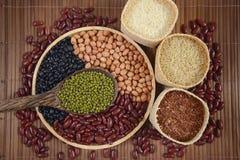Зерна хлопьев и фасоли семян полезные для здоровья в деревянных ложках на белой предпосылке Стоковые Изображения