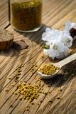 Зерна цветня пчелы в опарнике и деревянной ложке на деревянном столе с цветками деревьев весны Apitherapy Продукты пчелы Стоковое фото RF