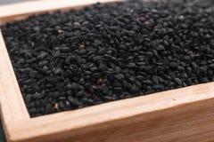 Зерна черных тимона и масла на деревенской предпосылке Стоковые Изображения