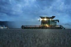 Зернокомбайн жать на сумерк Стоковые Изображения RF
