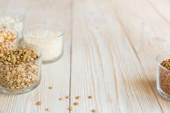 Зерно и фасоли в стеклянных шарах на белой деревянной предпосылке Стоковые Фотографии RF