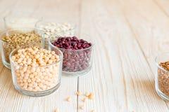 Зерно и фасоли в стеклянных шарах на белой деревянной предпосылке Стоковое Фото