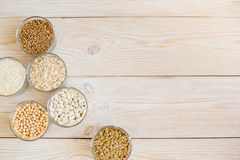 Зерно и фасоли в стеклянных шарах на белой деревянной предпосылке Стоковая Фотография