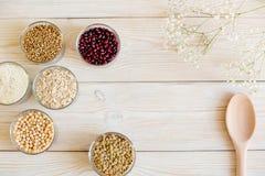 Зерно и фасоли в стеклянных шарах на белой деревянной предпосылке Стоковое фото RF
