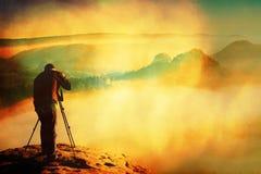 Зерно фильма Профессионал на скале Фотограф природы принимает фото с камерой зеркала на пике утеса Мечтательный ландшафт fogy стоковое изображение
