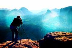 Зерно фильма Профессионал на скале Фотограф природы принимает фото с камерой зеркала на пике mountaiin стоковая фотография rf
