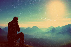 Зерно фильма Фотограф принимает фото с камерой зеркала на пике утеса Мечтательный ландшафт, оранжевое Солнце на горизонте Стоковая Фотография RF