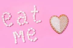 Зефиры на розовой предпосылке с подписывают внутри английское едят меня Плоские положение или взгляд сверху Предпосылка или текст Стоковое Изображение RF