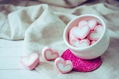 Зефиры формы сердца в белой кружке на деревянной предпосылке, сладостной Стоковое Изображение RF