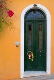 Зеленая дверь на оранжевой стене Стоковые Фотографии RF