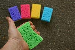 Зеленая губка в руке на фоне покрашенных губок на поле Стоковое Фото