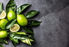 Зеленая известка лимона с свежими листьями на черной предпосылке шифера Стоковое Изображение RF
