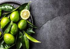 Зеленая известка лимона с свежими листьями на черной плите, предпосылке шифера Стоковые Фотографии RF