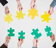 Зеленая и желтая головоломка соединяет в руках людей Стоковое Фото