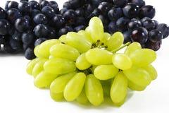 Зеленая и черная виноградина на белизне Стоковые Изображения