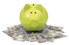 Зеленая копилка стоя на долларовых банкнотах изолированных над белизной Стоковое фото RF