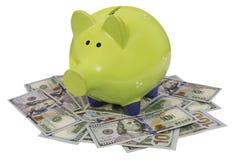 Зеленая копилка стоя на долларовых банкнотах изолированных над белизной Стоковые Изображения RF