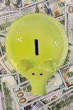 Зеленая копилка стоя на долларовых банкнотах Стоковые Фотографии RF