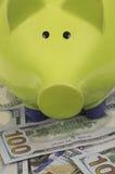 Зеленая копилка стоя на долларовых банкнотах Стоковое Фото