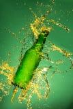 Зеленая пивная бутылка с брызгать жидкость стоковые изображения rf