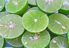Зеленая предпосылка с цитрусовыми фруктами кусков известки Стоковая Фотография RF