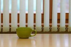 Зеленая пустая чашка на таблице Стоковое Изображение