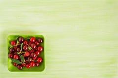 Зеленая плита с свежими вишней и полениками на зеленой деревянной предпосылке Стоковое Фото