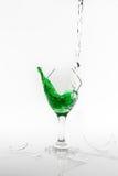 Зеленая расслоина воды от сломленного бокала на белой предпосылке Стоковые Изображения