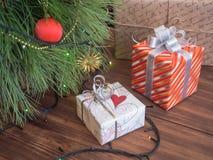 Зеленая рождественская елка украшенная с игрушками и гирляндой привела света Кладет подарки в коробку Стоковая Фотография RF
