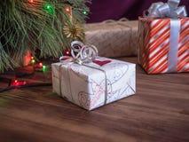 Зеленая рождественская елка украшенная с игрушками и гирляндой привела света Кладет подарки в коробку Стоковое Фото
