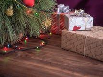 Зеленая рождественская елка украшенная с игрушками и гирляндой привела света Кладет подарки в коробку Стоковые Изображения RF