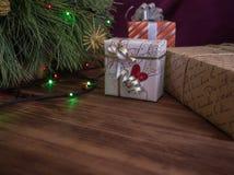 Зеленая рождественская елка украшенная с игрушками и гирляндой привела света Кладет подарки в коробку Стоковые Фотографии RF