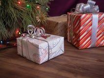 Зеленая рождественская елка украшенная с игрушками и гирляндой привела света Кладет подарки в коробку Стоковое фото RF