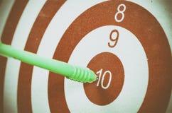 Зеленая стрелка дротика ударяя в центре цели dartboard Стоковое Изображение