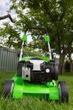 Зеленая травокосилка на зеленой лужайке Стоковые Изображения