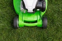 Зеленая травокосилка на зеленой лужайке Стоковое Фото