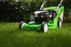 Зеленая травокосилка на зеленой лужайке Стоковые Фотографии RF
