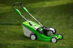 Зеленая травокосилка на зеленой лужайке Стоковое фото RF