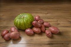 Зеленая тыква и свежие картошки на деревянной таблице, концепции, идее стиля еды деревенского Стоковое Изображение RF