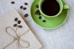 Зеленая чашка кофе с кофейными зернами и тетрадью Стоковые Изображения