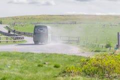 Зеленая шина на проселочной дороге и красивом взгляде ландшафта  Стоковая Фотография RF