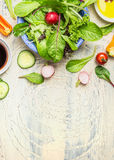 Зеленое блюдо салата страны с редиской, огурцом и томатами на светлой деревенской предпосылке, взгляд сверху стоковая фотография