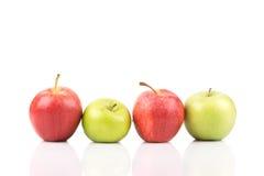 2 зеленое и красные яблоки стоя в ряд на белой предпосылке Стоковое фото RF