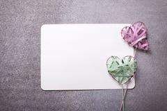 2 зеленое и розовые декоративные сердца и пустая бирка на сером sl Стоковые Фото